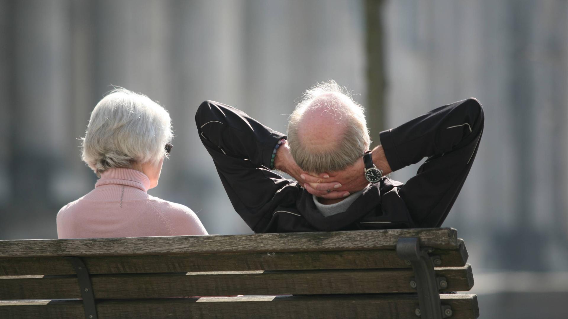 Ein Rentnerpaar sitzt auf einer Bank vor dem Reichstag und sonnt sich.