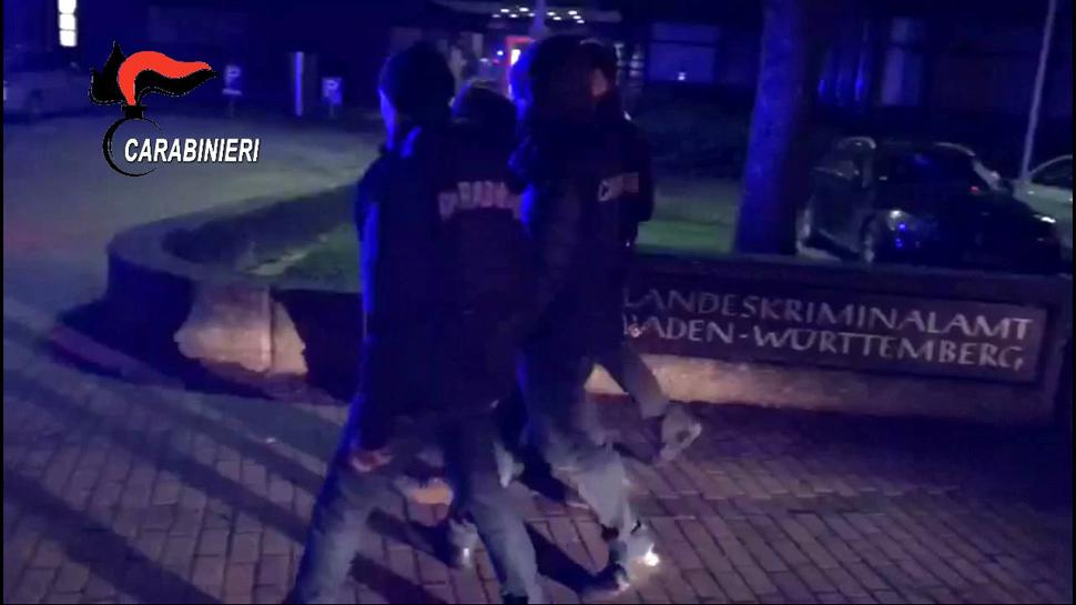 Der Screenshot aus einem Video der italienischen Gendarmerie zeigt Carabinieri, die am frühen Morgen des 9. Januar 2018 nach einer Razzia gegen den 'Ndrangheta-Clan Farao-Marincola inItalien und Deutschland einen Mafia-Verdächtigen in Stuttgart vor dem Landeskriminalamt abführen.