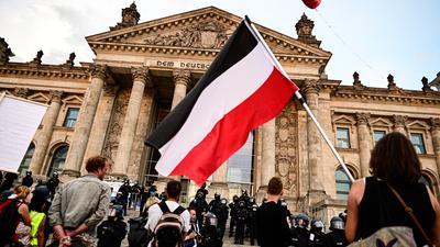 ARCHIV - 29.08.2020, Berlin: Teilnehmer einer Kundgebung gegen die Corona-Maßnahmen stehen vor dem Reichstag, ein Teilnehmer hält eine Reichsflagge. (zu dpa «D wie Drosten, Q wie Querdenken: Das ABC zum Krisenjahr 2020») Foto: Fabian Sommer/dpa +++ dpa-Bildfunk +++
