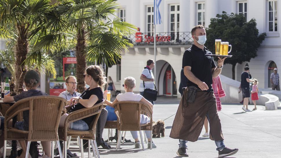 Gäste sitzen in einem Straßen-Cafe in Baden-Baden.