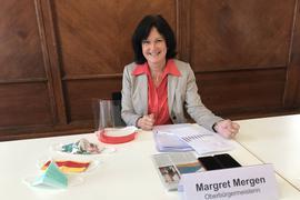 Baden-Badens OB Margret Mergen sitzt mit Visier und Maske an einem Tisch.