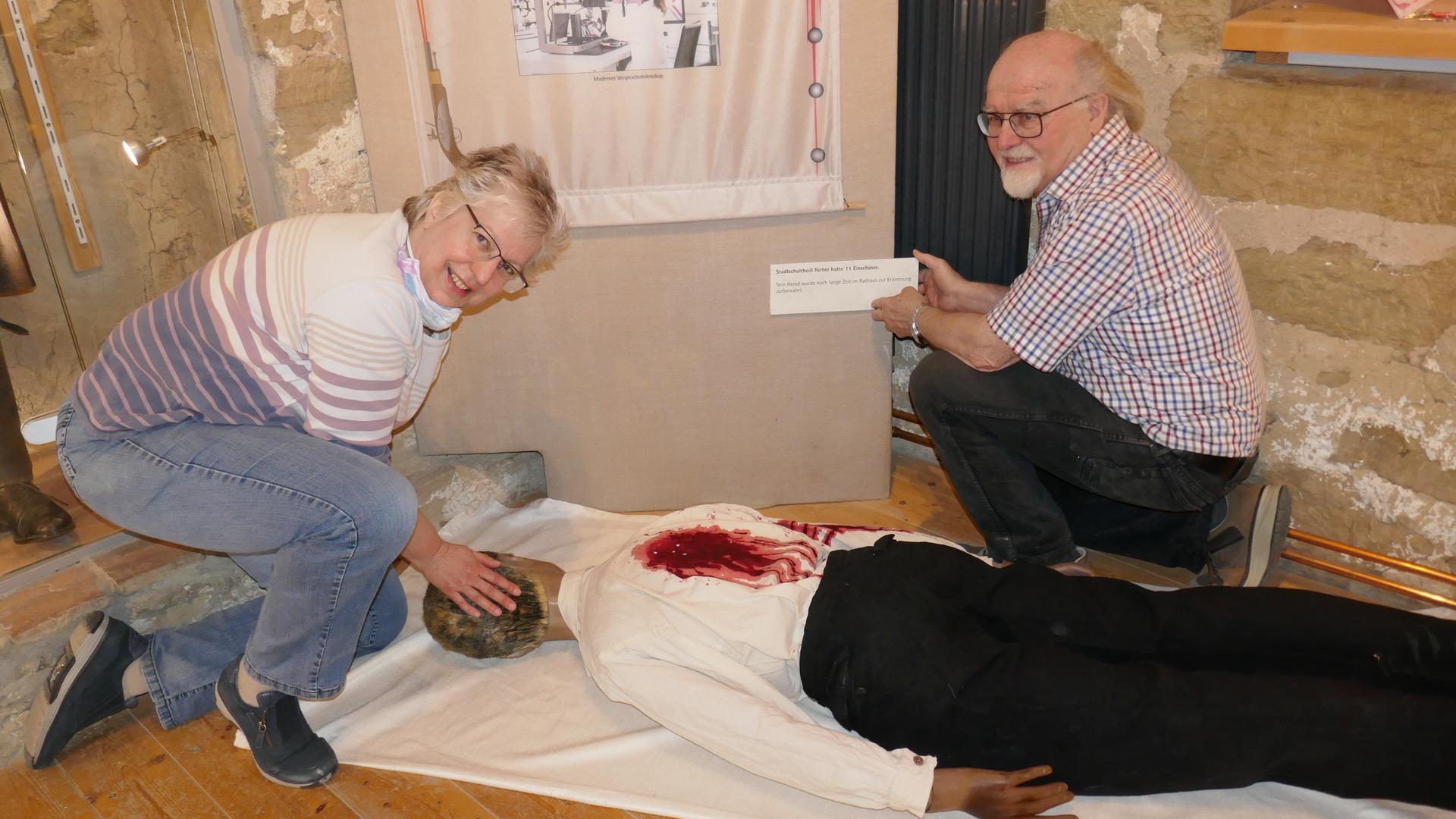 Ann Marie Ackermann und Karl Sartorius an einer Puppe, die den ermordeten Bürgermeister von Bönnigheim darstellt.