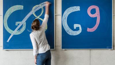 ILLUSTRATION - Eine Schülerin der Oberstufe streicht an einem Gymnasium den Schriftzug «G8» an einer Tafel durch, daneben lässt sie «G9» unberührt. +++ dpa-Bildfunk +++
