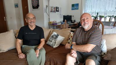 Hans Jürgen Sattler (links) sitzt auf seinem Sofa neben Klaus Schuhmann.