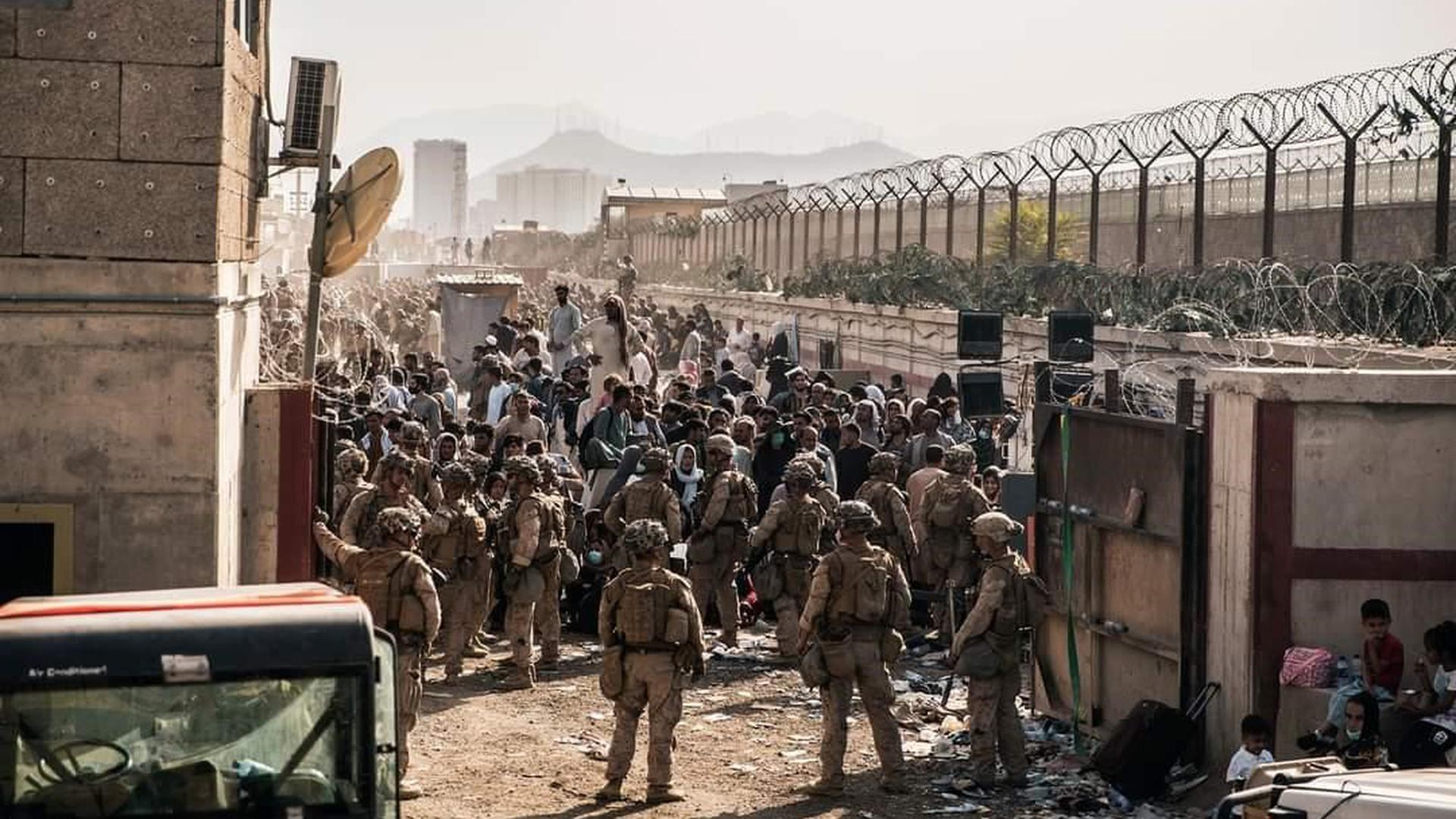 Kein Durchkommen: Ein Foto von der sicheren Seite zeigt, wie aussichtslos der Versuch der vielen wartenden Menschen vor den Toren des Flughafens Kabul ist.