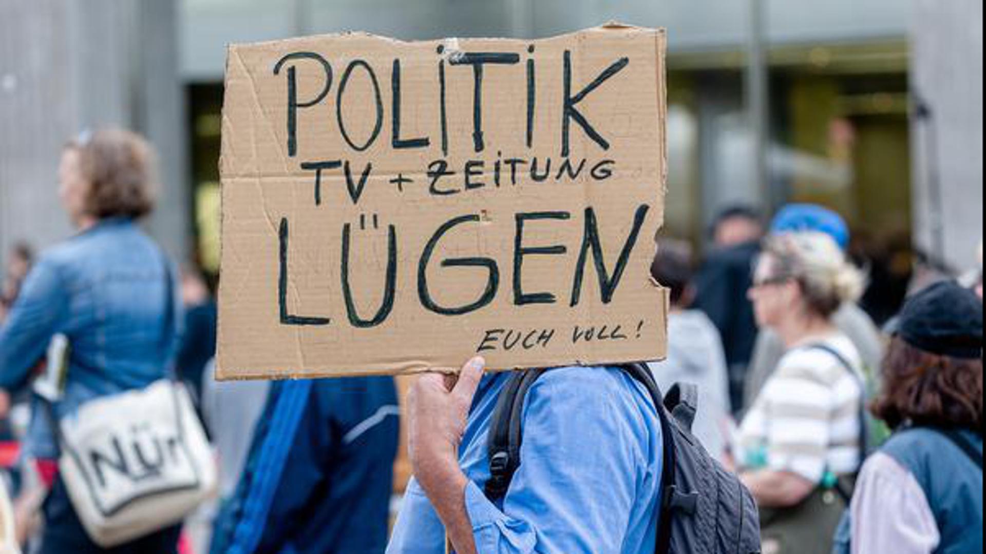 """Ein Mann hält bei einer Querdenken-Demonstration unter dem Motto """"Gemeinsam und gewaltfrei für die Aufhebung der Coronamaßnahmen"""" ein Plakat mit der Aufschrift """"Politik, TV und Zeitung lügen euch voll!"""" hoch."""