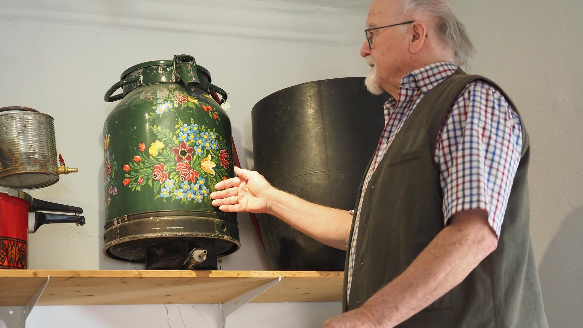 Kurt Sartorius, Gründer des Schwäbischen Schnapsmuseums Bönnigheim, steht auf einer Leiter und zeigt eine bemalte Milchkanne, in der ein Karlsruher einst illegal Schnaps brannte.