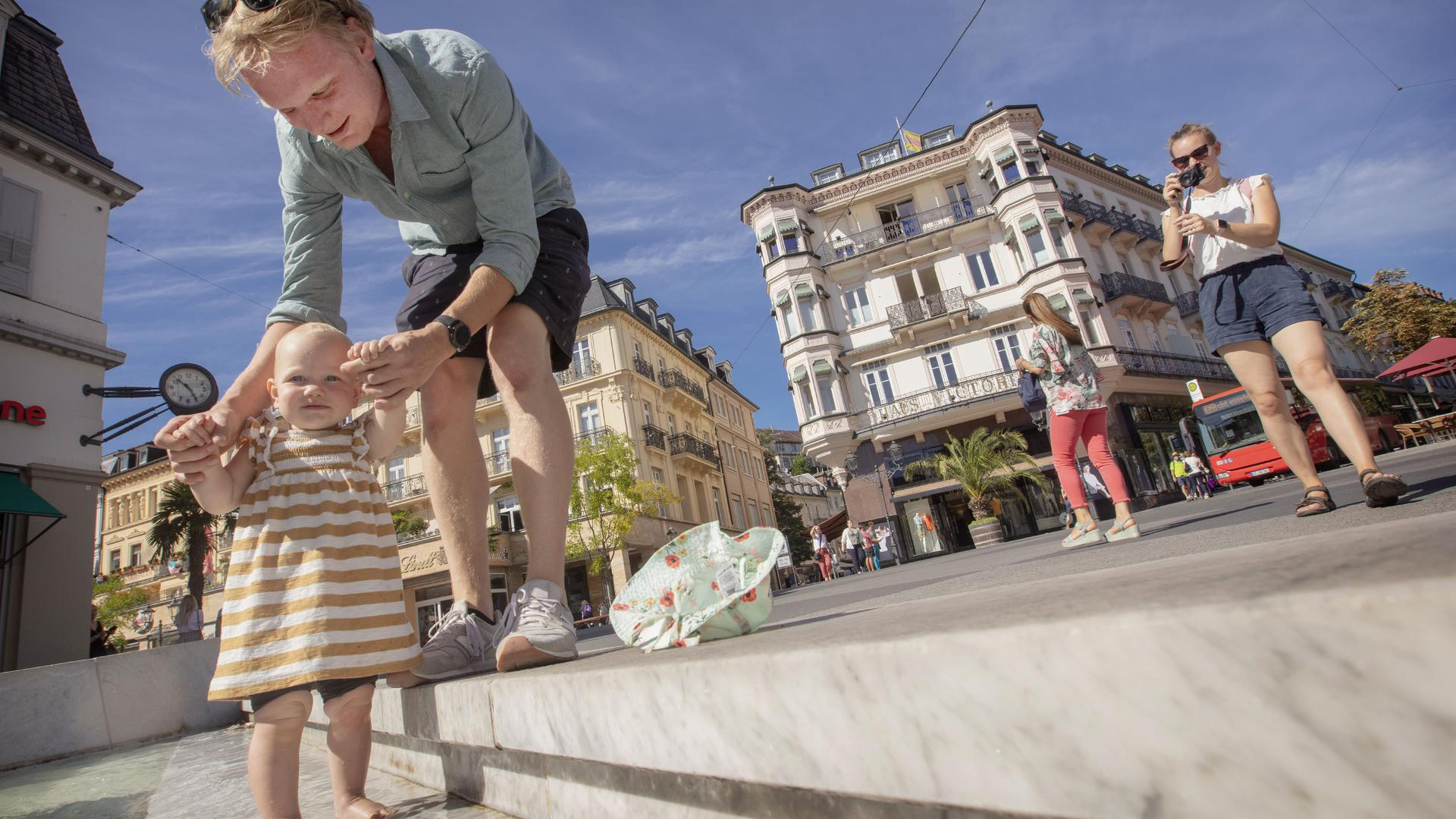Eine junge Familie mit Kind aus Finnland sucht Abkühlung im Brunnen am Leopoldsplatz in Baden-Baden.