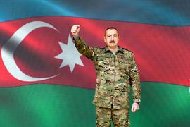 Ilham Aliyev, Präsident von Aserbaidschan, steht in Baku vor einer Projektion der Nationalflagge.