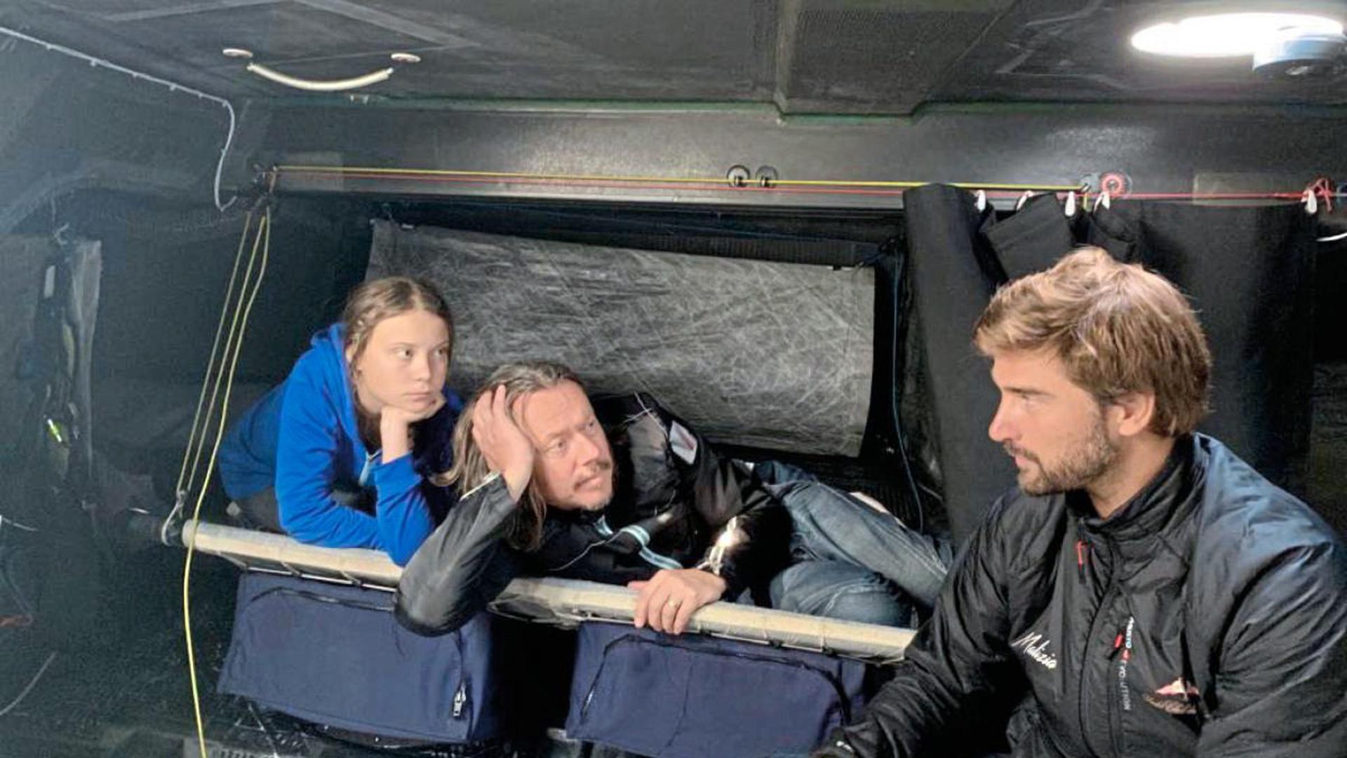 """Starten Richtung Westen: Profisegler Boris Hermann (rechts), Greta Thunberg und ihr Vater Svante an Bord der """"Malizia"""", die keinerlei Komfort bietet."""
