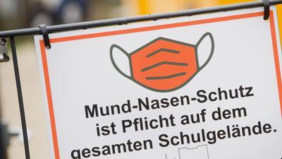 Der Schriftzug «Mund-Nasen-Schutz ist Pflicht auf dem gesamten Schulgelände» und ein Piktogramm einer Maske sind auf einem Schild am Eingang einer Schule zu sehen.