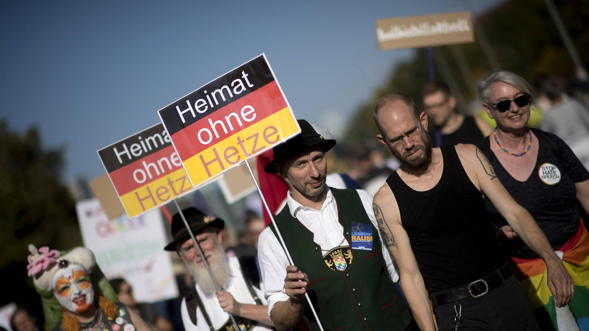 Demonstranten mit Plakaten in Schwarz-Rot-Gold, auf denen steht: Heimat Ohne Hetze.
