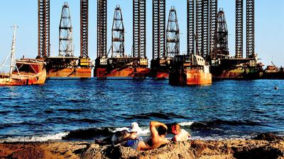 A picture made available 29 July shows workers from Oil platforms enjoy the sun on the beach of Caspian See near Azerbaijan capital city Baku, 23 July 2008. Crude oil prices above 120 US dollars a barrel are abnormal and could fall to around 78 US dollars under the right circumstances, OPEC President Chakib Khelil said in Jakarta on 29 July 2008. EPA/FILIP SINGER +++ dpa-Bildfunk +++