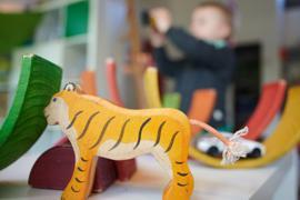Ein Junge spielt in der Kita mit Bauklötzen und einem Spielzeugauto.