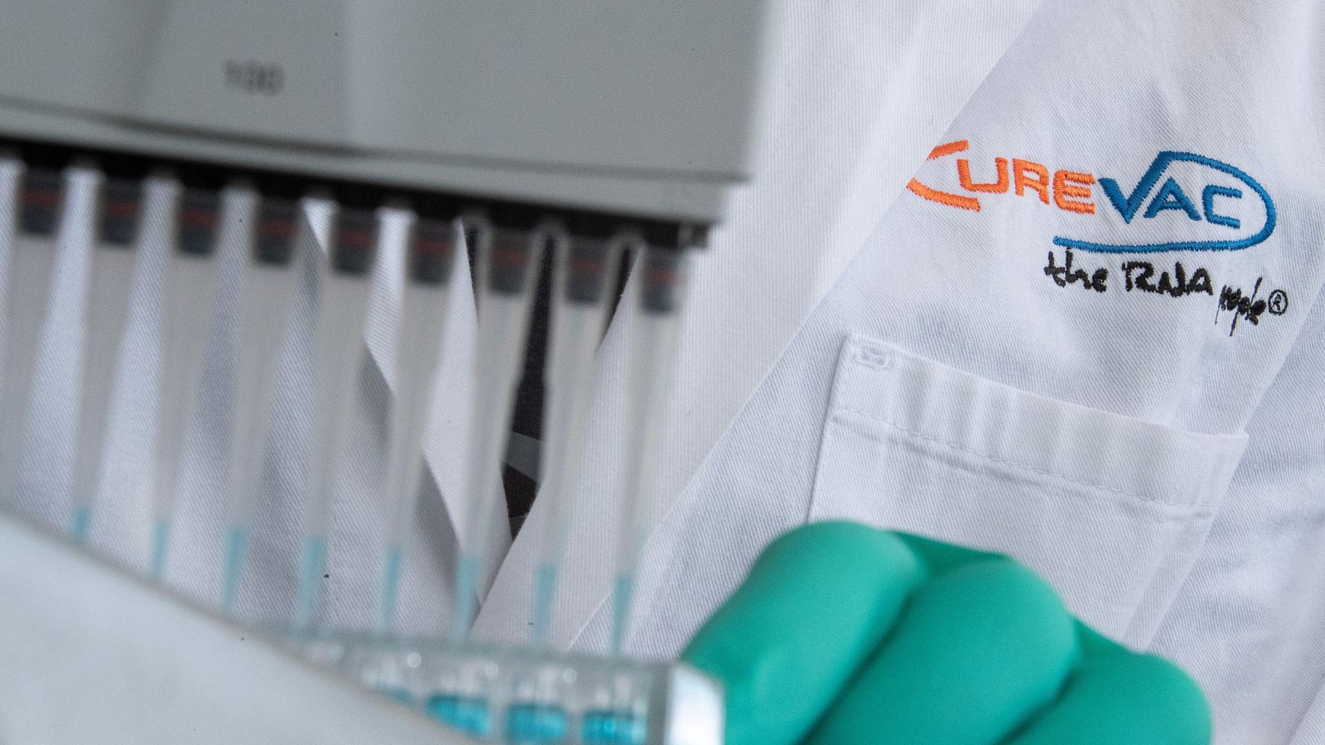 Ein Mann pipettiert in einem Labor des biopharmazeutischen Unternehmens CureVac eine blaue Flüssigkeit.