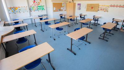 Stühle und Tische stehen im Abstand von jeweils zwei Metern in einem Klassenzimmer.