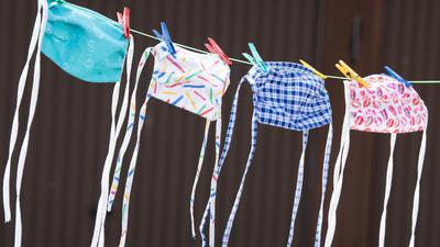 Mundschutze hängen auf einer Wäscheleine nebeneinander.