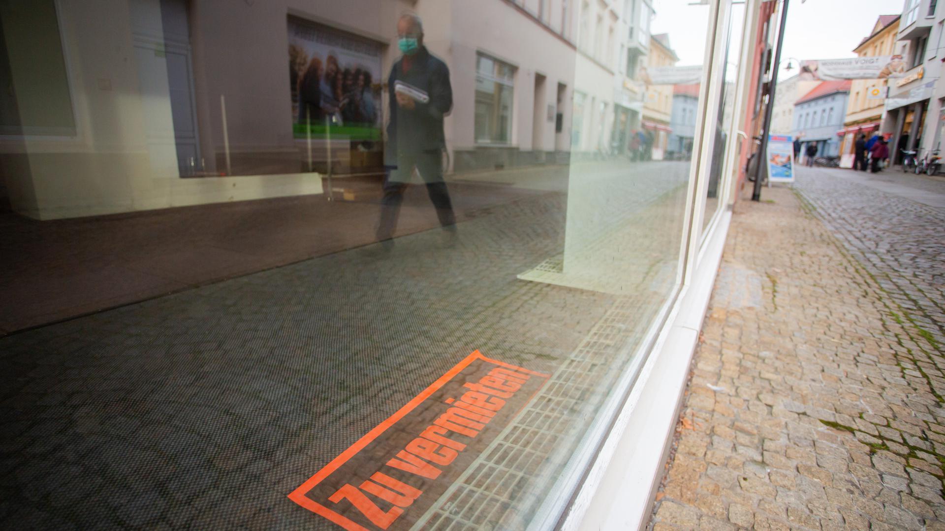 """dpatopbilder - 14.12.2020, Brandenburg, Senftenberg: """"Zu vermieten"""" steht in Senftenberg im südbrandenburgischen Landkreis Oberspreewald-Lausitz in einem leeren Geschäft in einer Einkaufsstraße. Die Bundeskanzlerin und die Ministerpräsidenten der Länder haben einen harten bundesweiten Lockdown ab dem 16. Dezember beschlossen. Foto: Christoph Soeder/dpa +++ dpa-Bildfunk +++"""
