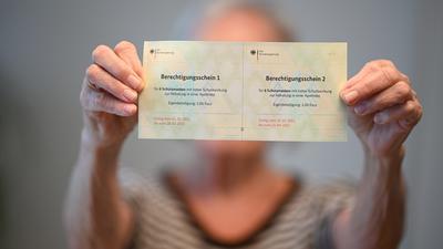 28.01.2021, Baden-Württemberg, Ravensburg: ILLUSTRATION - Eine Seniorin hält zwei Berechtigungsscheine von der Bundesregierung für jeweils sechs Schutzmasken mit hoher Schutzwirkung in den Händen. (gestellte Szene) Innerhalb von zwei verschiedenen Zeiträumen können sich die Empfänger der Berechtigungsscheine jeweils sechs FFP2-Masken in Apotheken abholen - für eine Zuzahlung von zwei Euro. Foto: Felix Kästle/dpa +++ dpa-Bildfunk +++