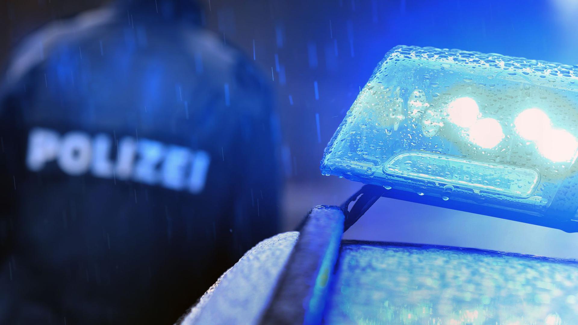 Ein Polizist steht vor einem Streifenwagen dessen Blaulicht aktiviert ist.