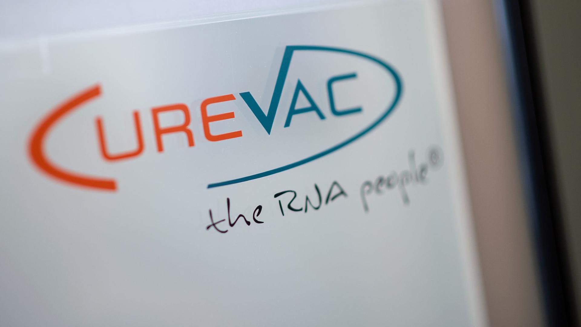 """Das Logo des biopharmazeutischen Unternehmens CureVac steht mit dem Slogan """"the RNA people"""" auf einer Scheibe."""