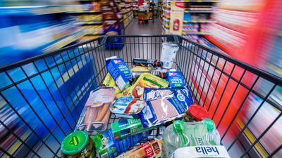 Ein Einkaufswagen mit Lebensmitteln wird durch die Regalreihen in einem Supermarkt geschoben.