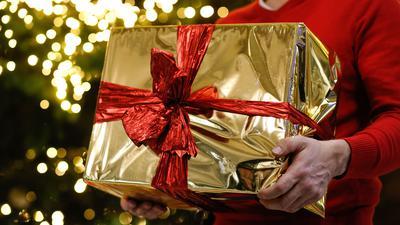 ARCHIV - 13.12.2018, Berlin: ILLUSTRATION - Ein Mann hält ein golden eingepacktes Weihnachtsgeschenk in den Händen. Im Hintergrund ist ein Weihnachtsbaum zu sehen. Foto: Gerald Matzka/dpa-Zentralbild/dpa +++ dpa-Bildfunk +++