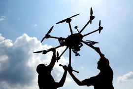 Andreas Volkert (r) und Joonas Lieb (l), wissenschaftliche Mitarbeiter im Deutschen Zentrum für Luft- und Raumfahrt (DLR), hantieren mit einer Forschungsdrohne in Cochstedt.