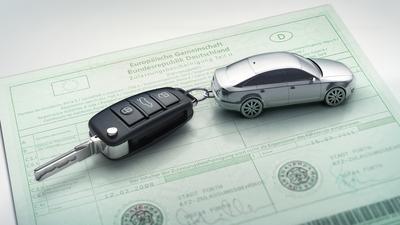 Eine Zulassungsbescheinigung mit einem Autoschlüssel.