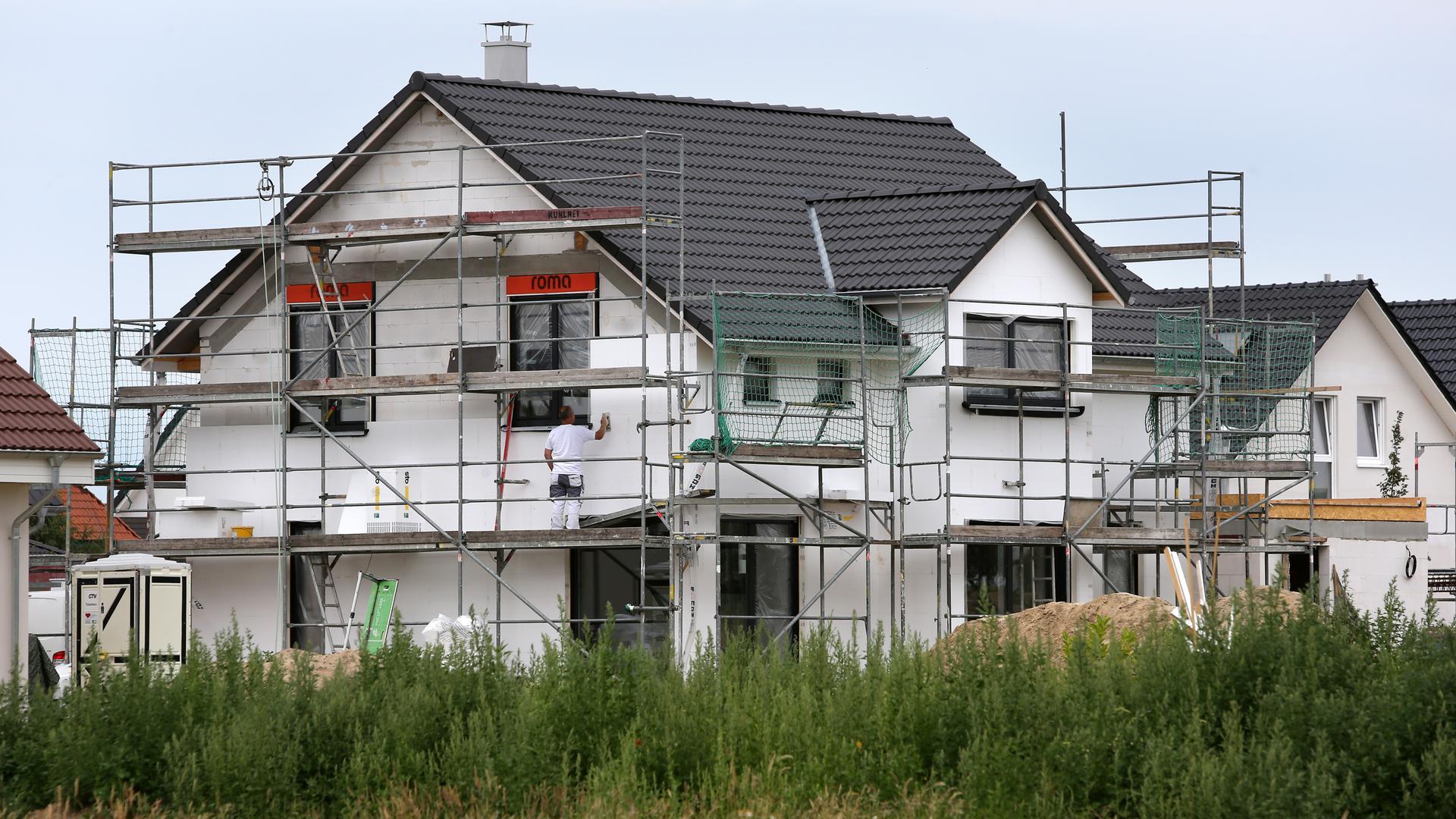 Bauarbeiter arbeiten an der Fertigstellung von Einfamilienhäusern.