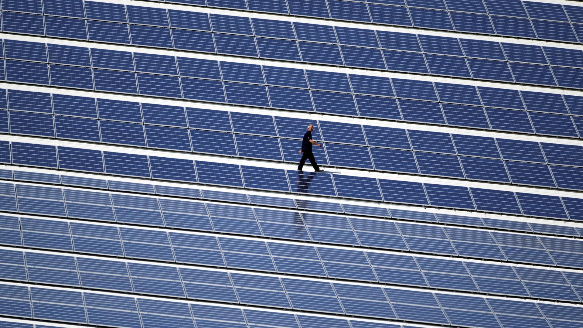 Ein Techniker geht über ein Dach, auf dem eine Photovoltaik-Anlage montiert wurde.