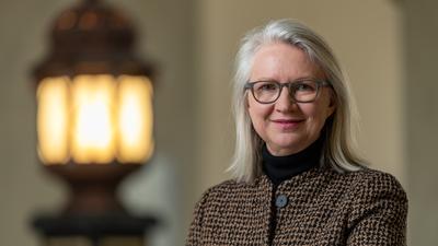 Monika Schnitzer, Wirtschaftsweise, steht im großen Treppenhaus der Ludwig Maximilian Universität.