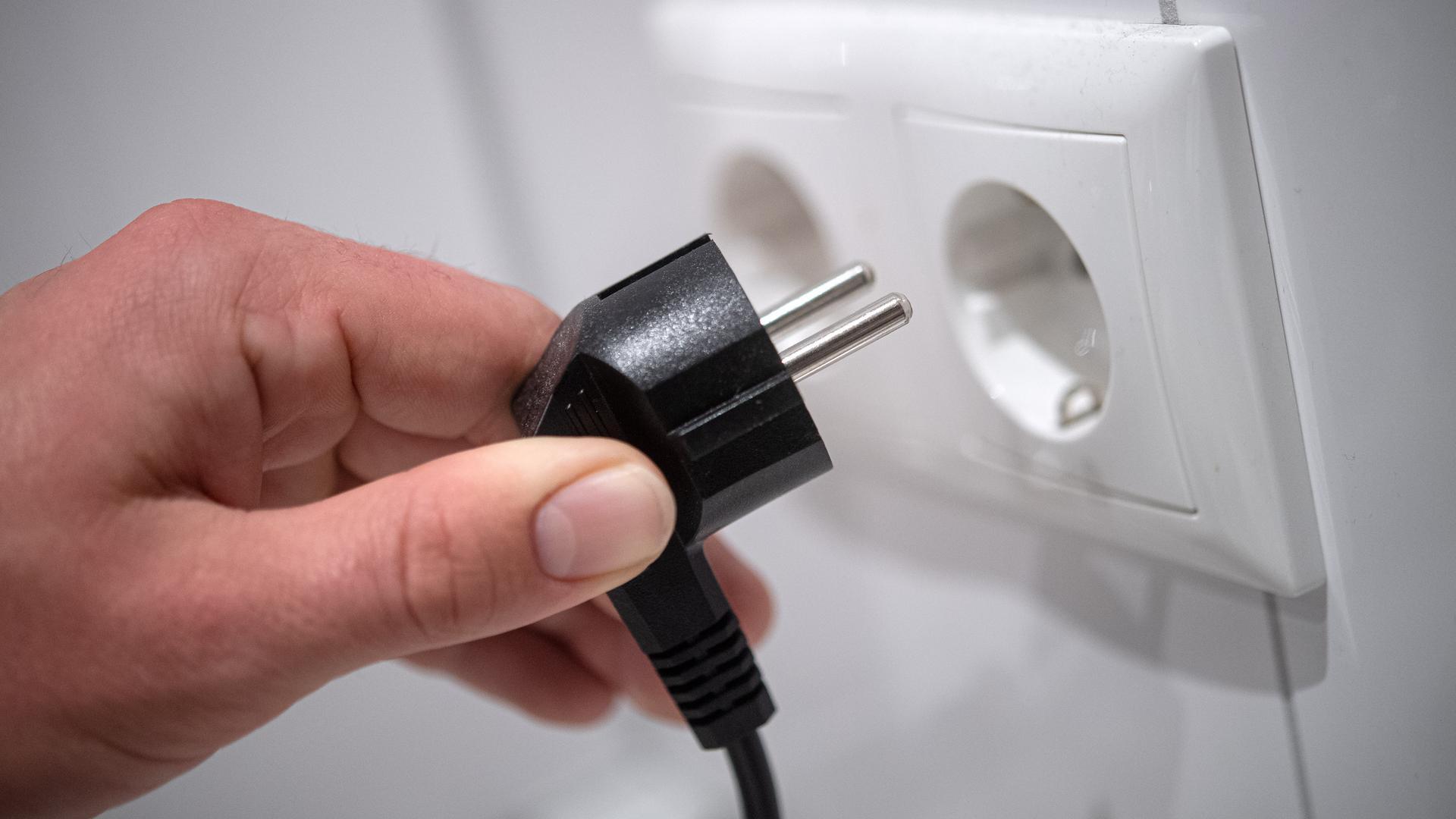 Ein Stecker wird in eine Steckdose gesteckt.