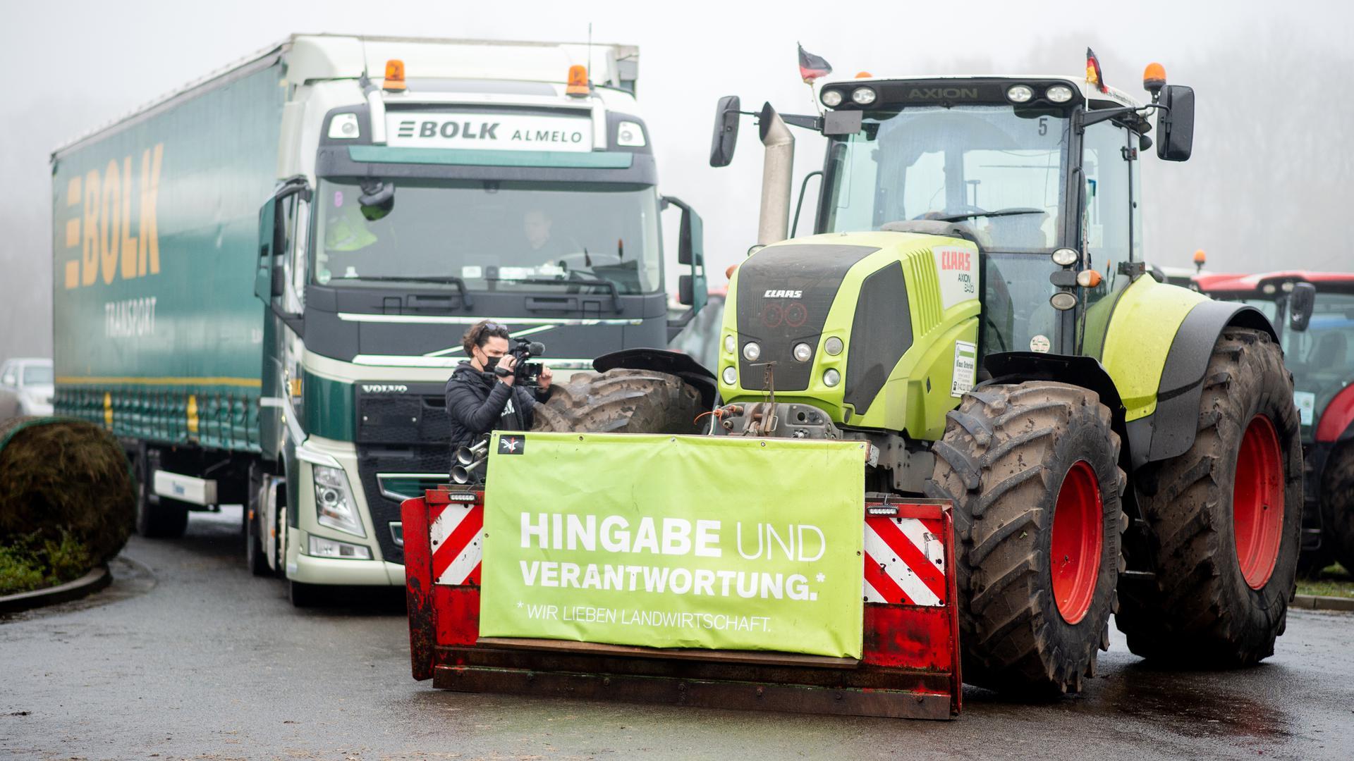 """Ein Traktor, an dem ein Transparent mit der Aufschrift """"Hingabe und Verantwortung"""" befestigt ist, blockiert die Zufahrt zum Zentrallager von Lidl."""