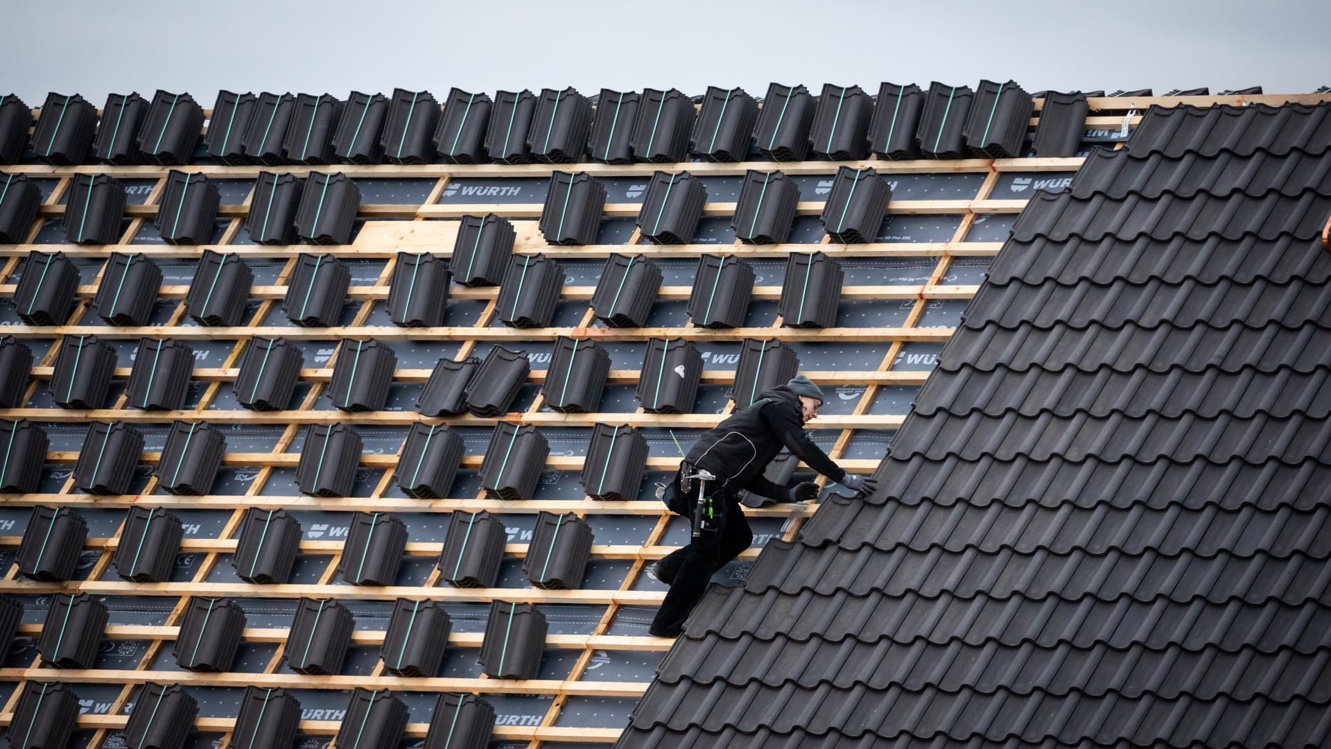 Ein Dachdeckermeister setzt eine Dachpfanne auf der Dachfläche eines Schulgebäudes.