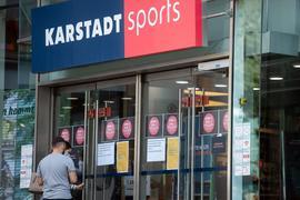 Passanten vor einem Eingang einer Filiale von Karstadt Sports.