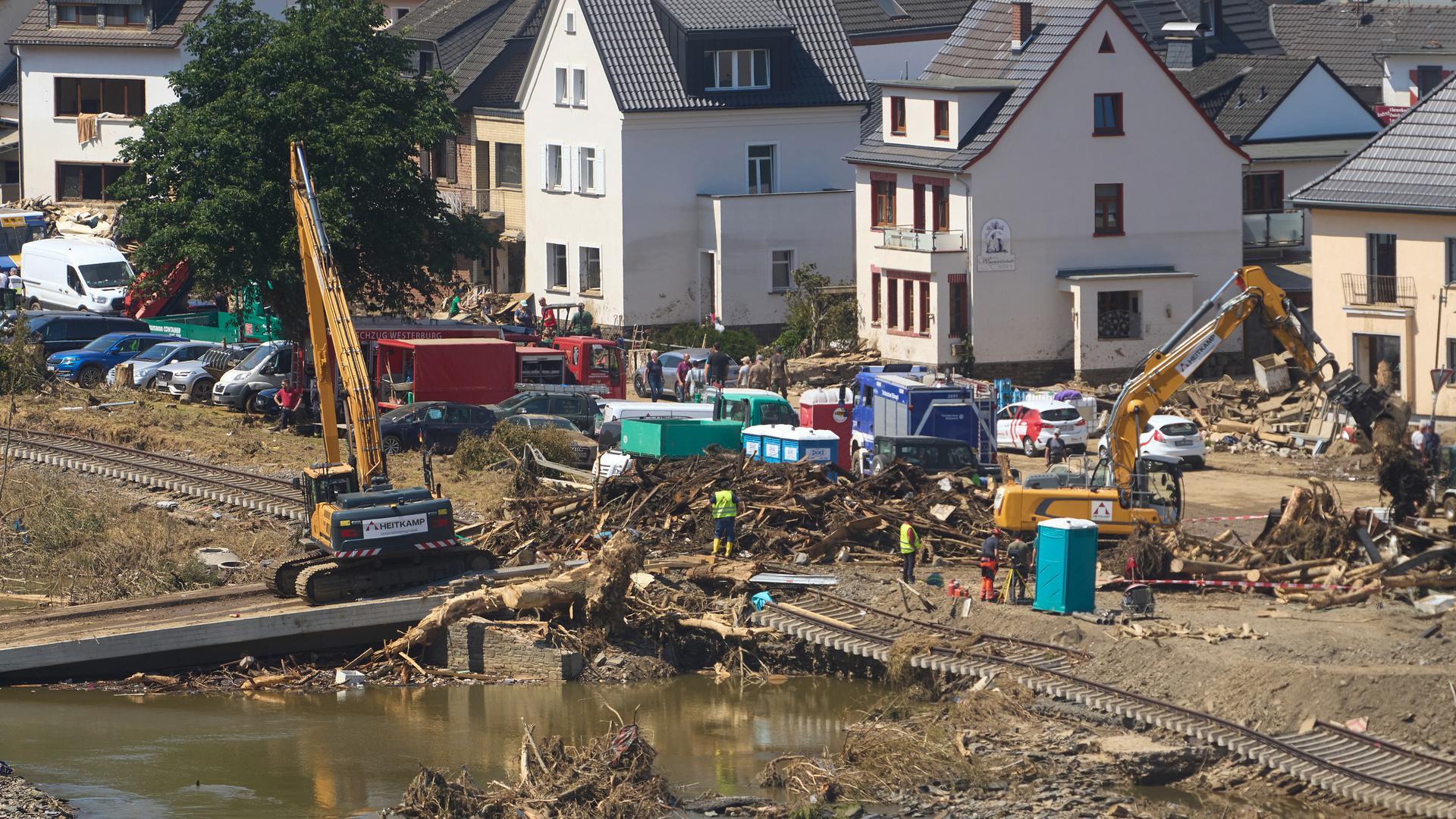 Bagger beseitigen nach dem Hochwasser den Schutt. Die Flut hat auch hier zahlreiche Häuser zerstört.