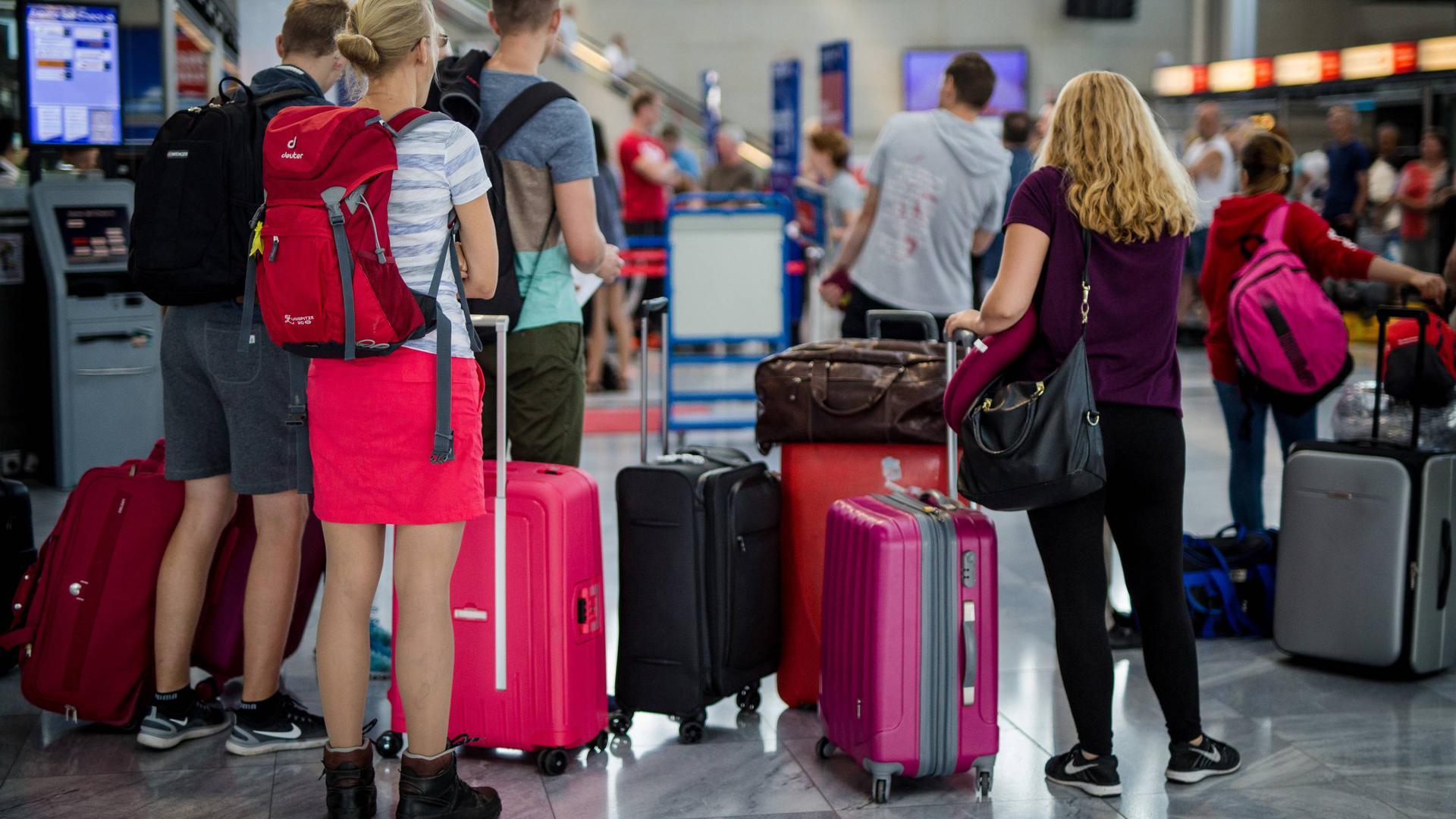 Passagiere warten im Terminal des Stuttgarter Flughafens darauf, ihr Gepäck abgeben zu können.