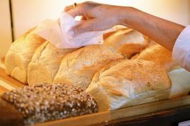 Eine Verkäuferin greift in einer Bäckerei und Konditorei nach einem Weißbrot.