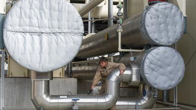 Ein Mitarbeiter steht  in einem Geothermiekraftwerk zwischen mehreren Behältern, die zum Austausch der Wärme genutzt werden.