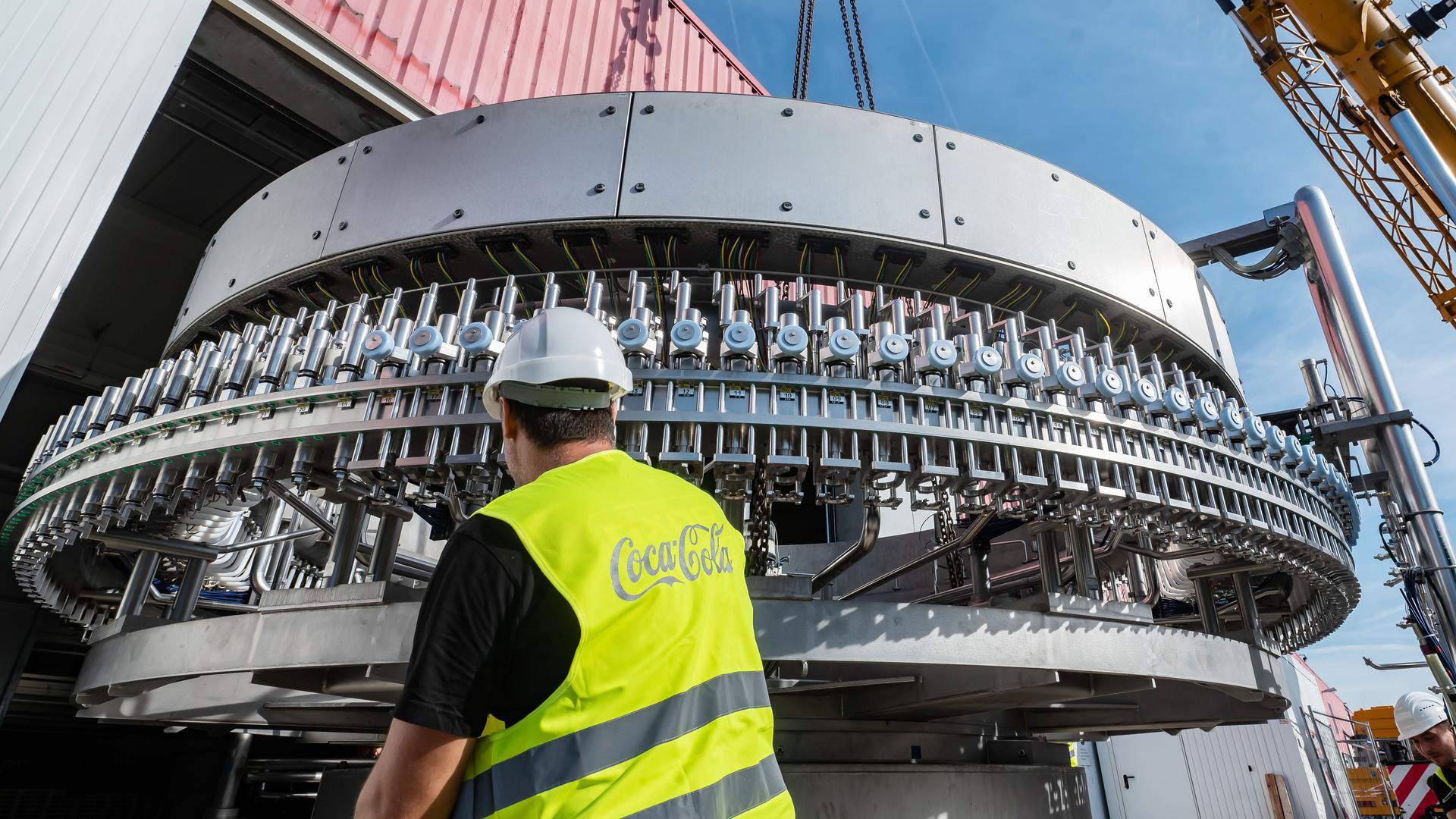 Der sogenannte Füller wird auf Schwerlastrollbrettern in die Produktionshalle von Coca-Cola in Karlsruhe gebracht. Zwischen Werkstor und Füller ist nur einen Finger breit Platz.