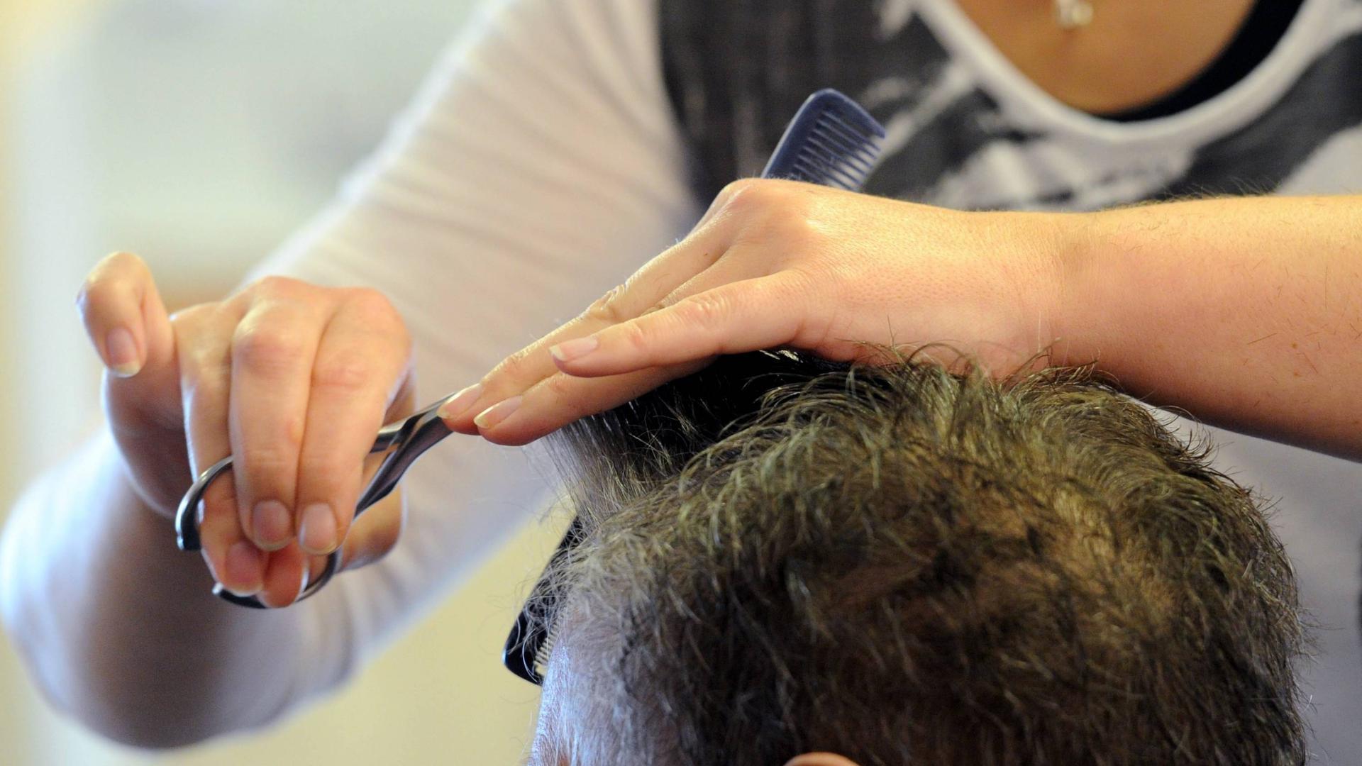 Eine Friseurin frisiert  einen Kunden.