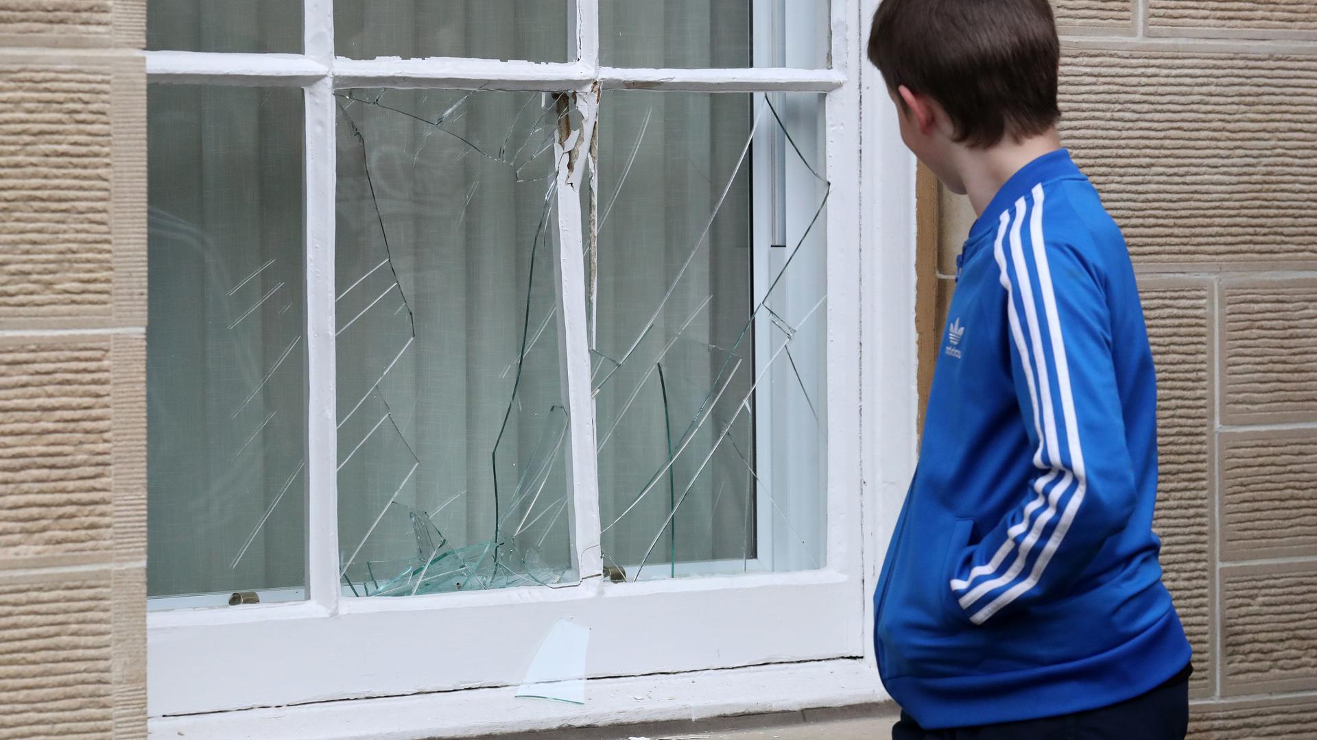Ein Junge schaut auf ein kaputtes Fenster