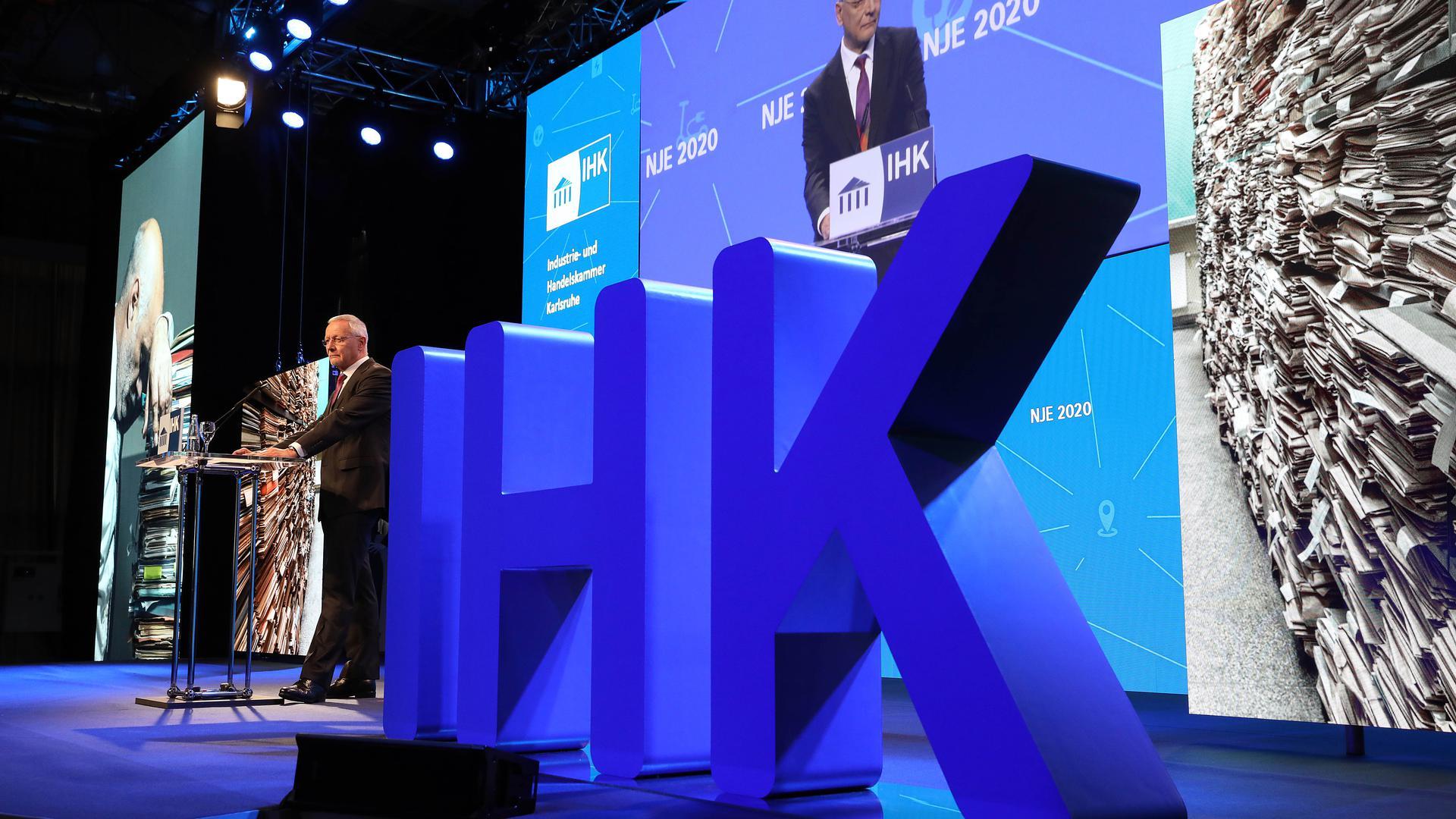 IHK-Emblem und IHK-Präsident Wolfgang Grenke