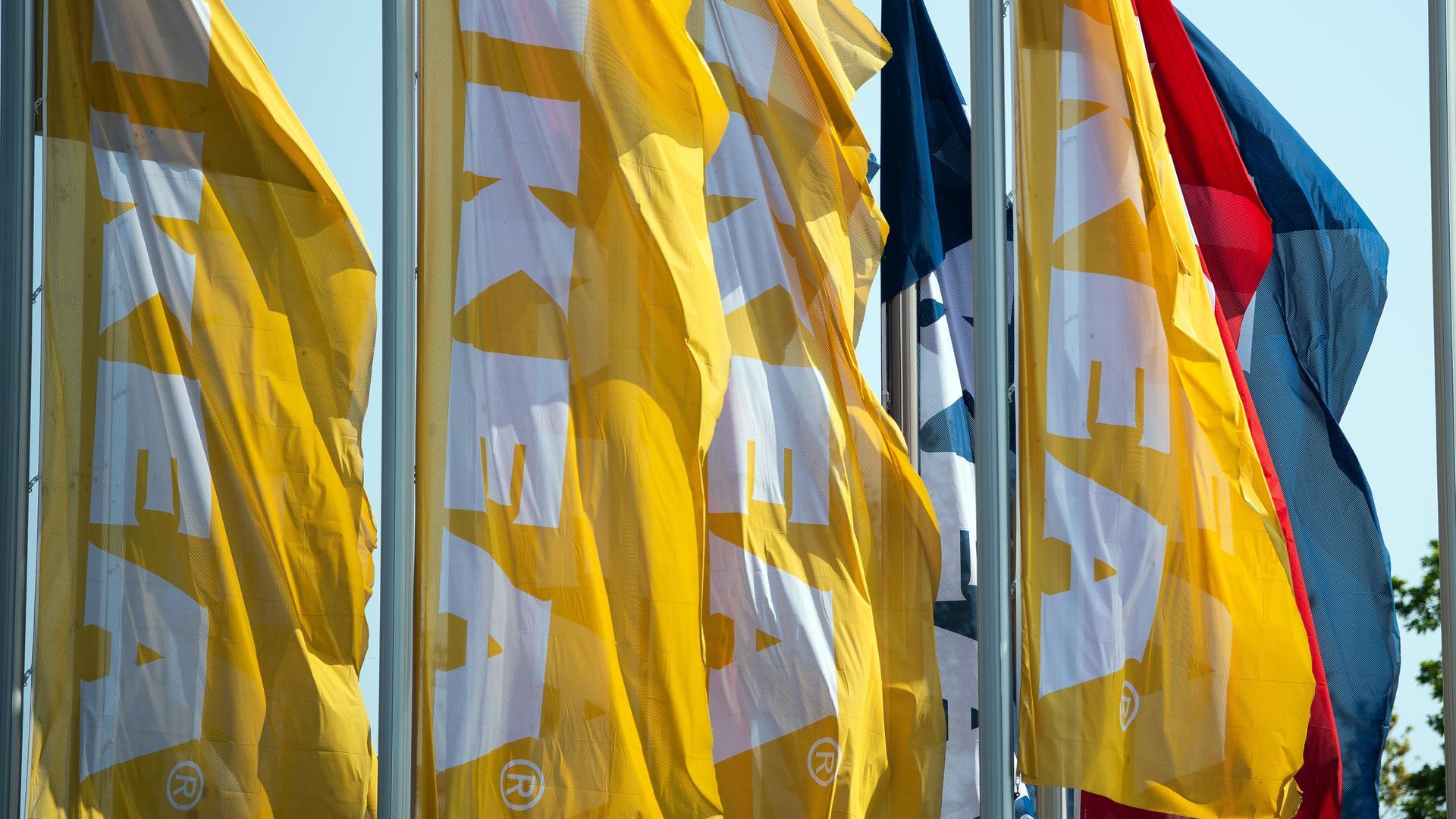 Fahnen mit dem Schriftzug IKEA wehen vor einem Möbelhaus im Wind.