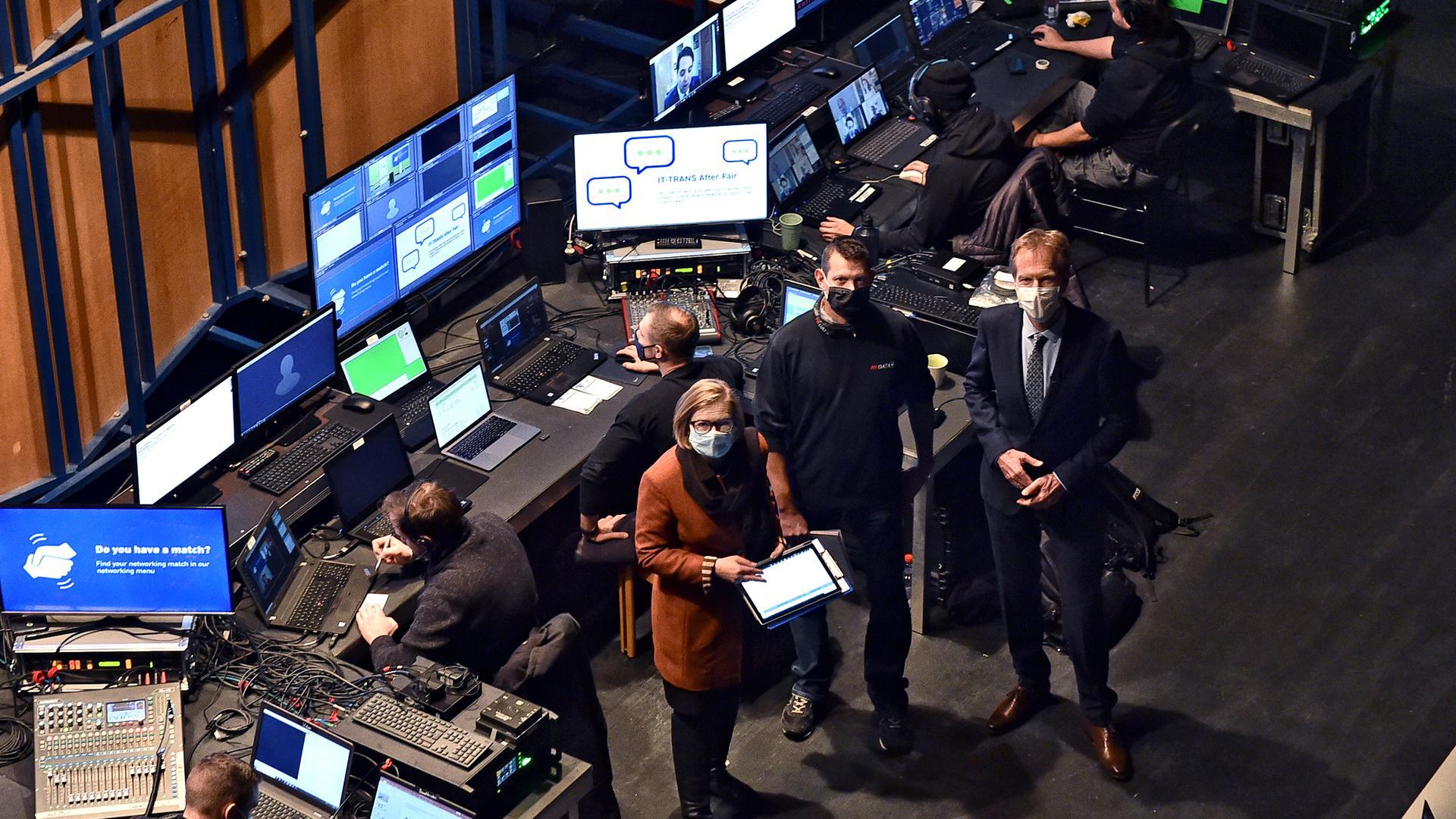 Hinter der Bühne ist die Technikzentrale der Fachmesse IT-Trans. Mit auf dem Bild (von links): Messe-Chefin Britta Wirtz, Jens Schürer von der Firma AVData und Moderator Markus Brock.
