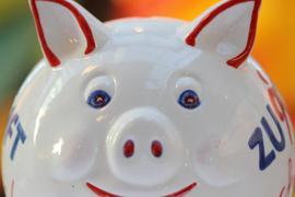 Ein Sparschwein steht auf einem Tisch.