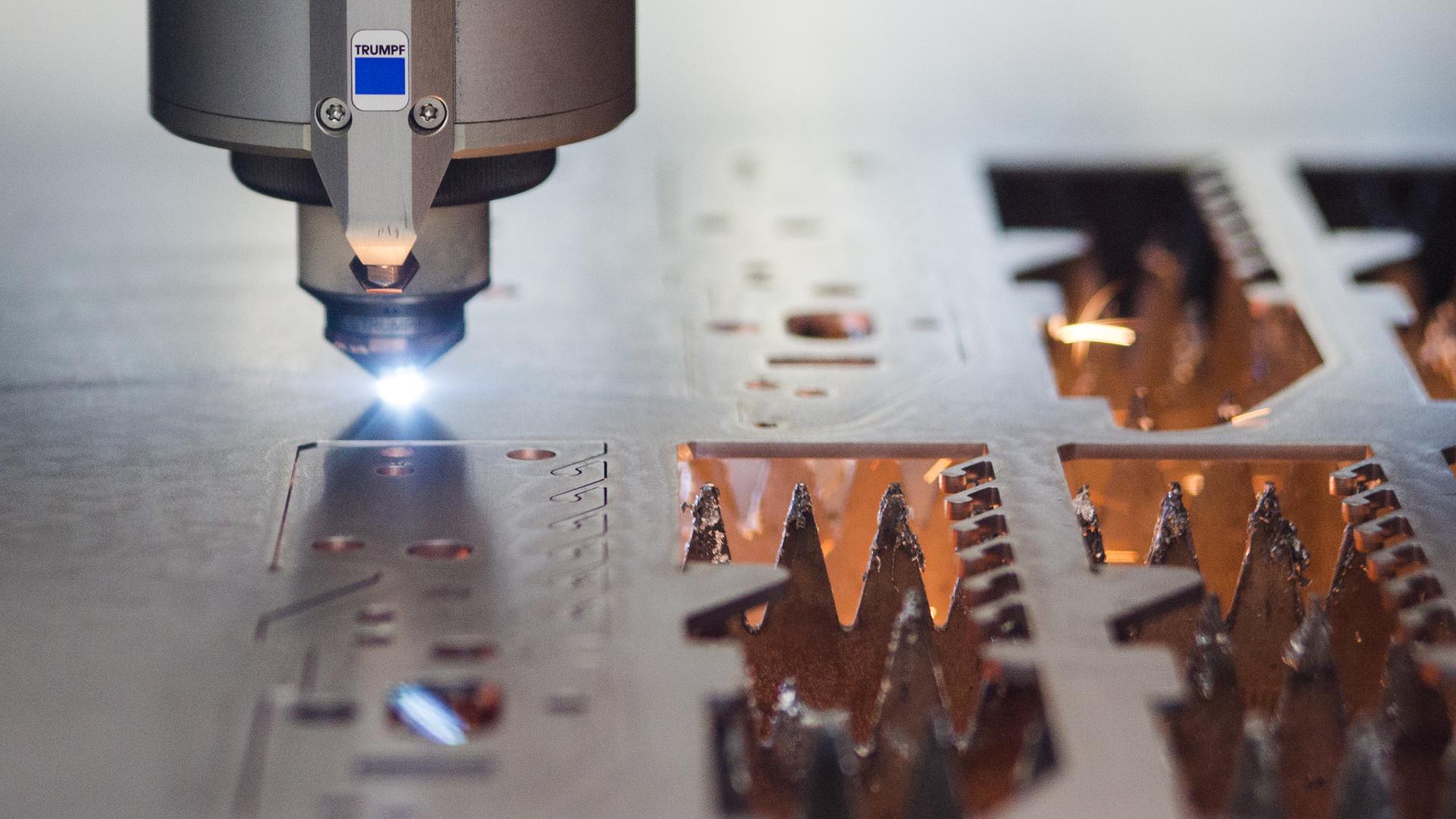 Ein Laser des Maschinenbauers Trumpf GmbH & Co. KG schneidet  in einer Produktionshalle  auf einer Platte.