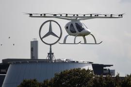 Ein sogenannter Volocopter fliegt neben einem Mercedes-Stern.+++