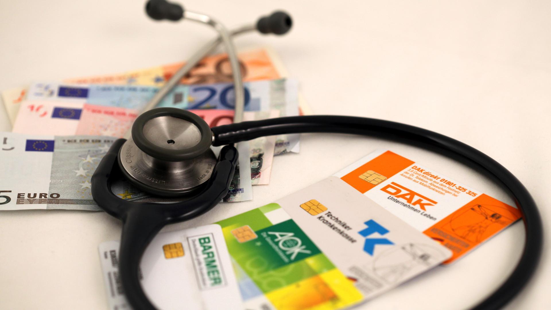 Die Versichertenkarten der Krankenkassen DAK, AOK, Barmer und Techniker-Krankenkasse TK liegen mit Euro-Geldnoten unter einem Stethoskop